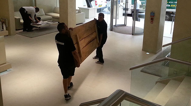 Two gladiator removal men carrying a crate through a lobby,